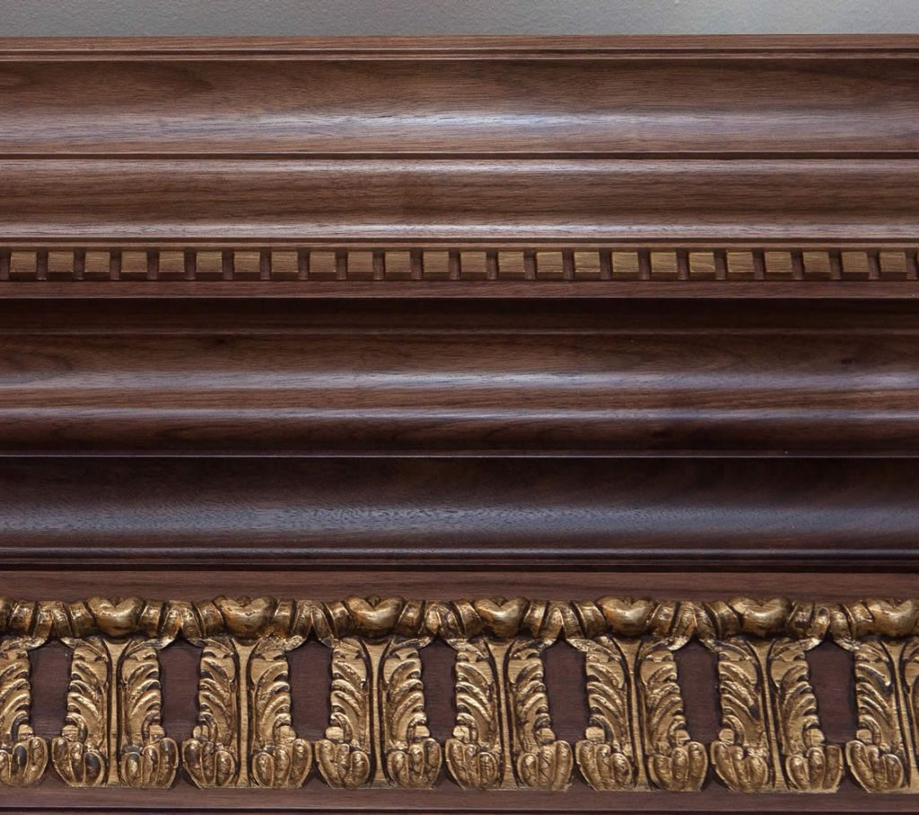 Interior cabinetry and panelling designed by Pan's Lodge and manufactured by one of our preferred workshops know for their outstanding specialist skills and craftsmanship. Dentil cornice detail showing acanthus leaf frieze hand carved from walnut.<br>Private Residence. London. 2015.