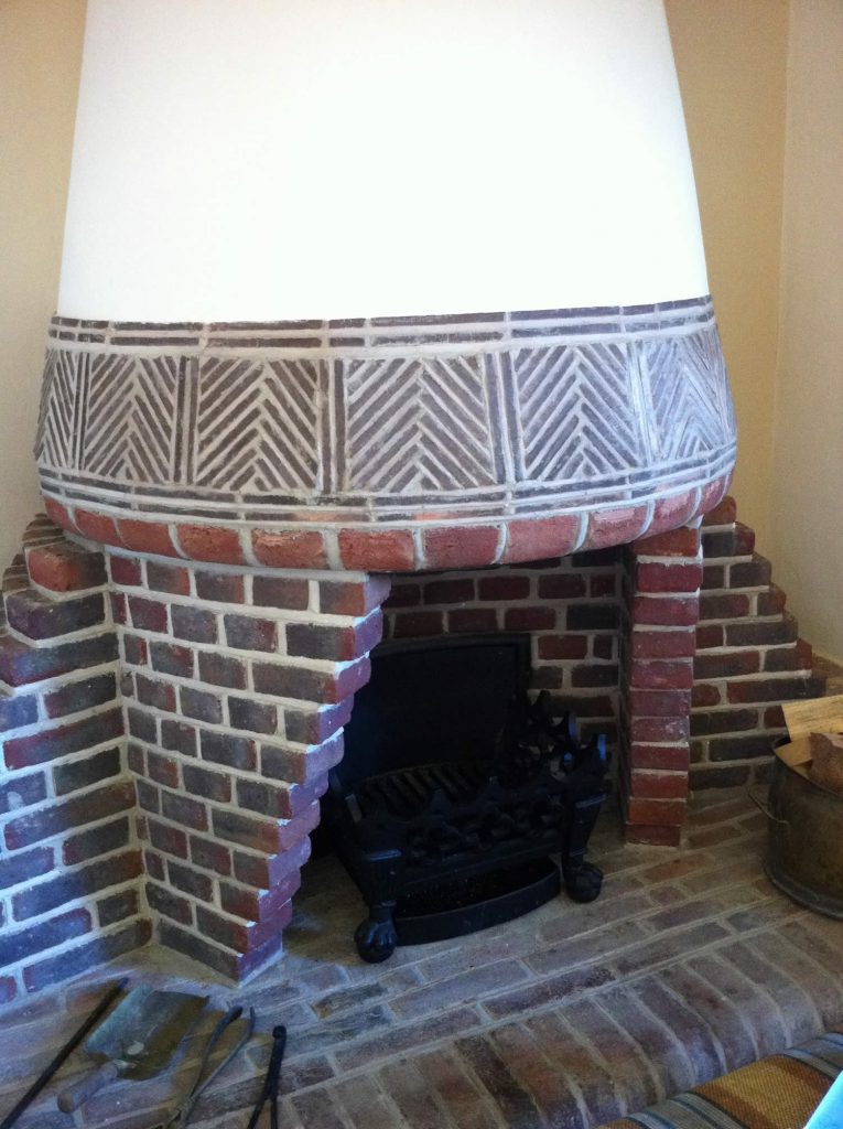 Conical shaped feature fireplace based on an original Arts & Crafts design. Brick, tile and plaster finishes.<br>Private Residence. West Sussex. 2008.