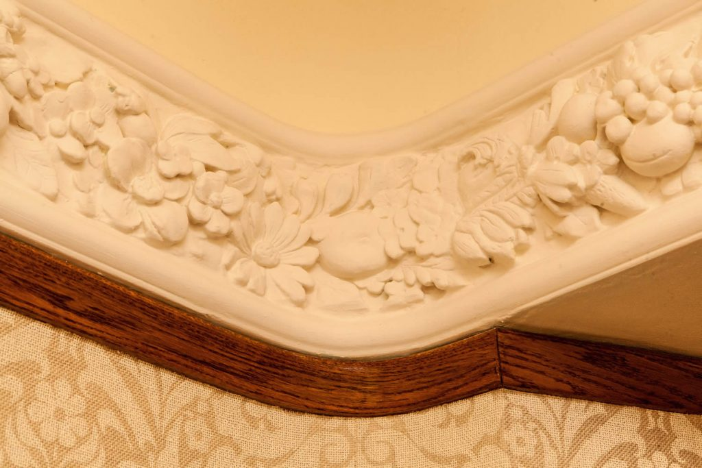 "<a href=""http://www.panslodge.com/products/plaster-mouldings/flora-plaster-frieze/flora-hand-cast-plaster-frieze/"">Flora hand cast plaster frieze</a> installed in an <i>Arts & Crafts residence</i>. Inspired by the carvings of <i>Grinling Gibbons</i>, the Flora Plaster Frieze is a hand cast repeatable design incorporating flowers, fruit and decorative shellwork, and is now part of our Architectural Plaster Mouldings Collection.<br>Private Residence. West Sussex. 2008. <br><br> ""The plasterwork frieze designed by Carmen for our coastal Arts & Crafts home is stunning. Drawing on a tremendous depth of knowledge, an original mould was re-modelled and adapted by skilled craftsmen to include exquisite and intricate detailing. Pan's Lodge Interior Design provide a wonderfully unique and professional service, and Carmen's meticulous attention to quality and detail ensures the most splendid results."" <br> Mrs. J., Winchester"