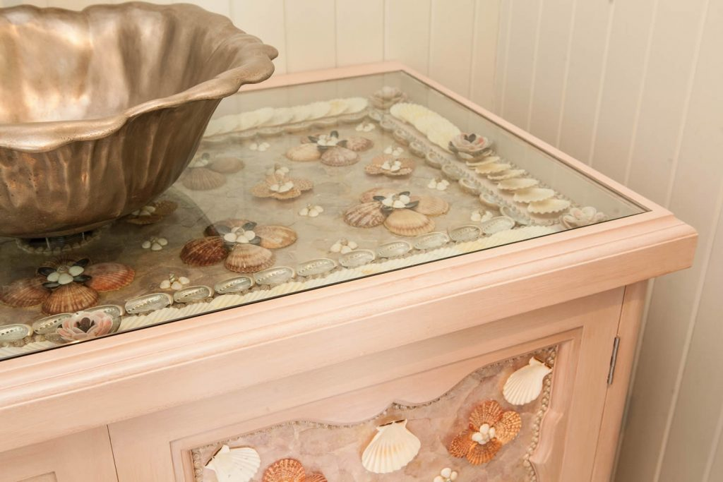 Decorative shellwork cabinet designed in collaboration with specialist shellwork artist <i>Tess Morley</i>. Featuring a large shell panel design set below glass cabinet top and matching door panels.<br>Private Residence. West Sussex. 2008.