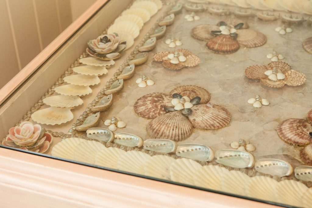 Detail of shellwork cabinet designed in collaboration with specialist shellwork artist <i>Tess Morley</i>. Featuring a large shell panel design set below glass cabinet incorporating oyster shells, cowries and scallop shells.<br>Private Residence. West Sussex. 2008.