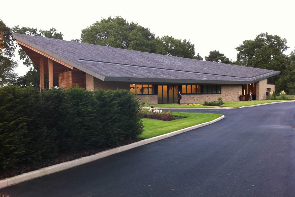 """Exterior view of the contemporary style Kemnal Park funeral chapel set within a 55 acre landscaped site including memorial gardens.<br>Public Space. Designed by <i><a href=""""http://www.openarc.co.uk/"""" target=""""_blank"""" rel=""""noopener noreferrer"""">OPEN Architecture, RIBA</a></i>. Kemnal Park Funeral Chapel and Memorial Gardens, Chislehurst, Kent. 2012/2013. <br><br> """"We feel that Pan's Lodge offered our client a measured, considered and ultimately hugely successful interiors solution, involving a subtle material and textural palette accentuating the architecture and recognising the sensitive and intimate nature of the building and its purpose. The personable approach and level of care for detail sets them apart from many others."""" <br> Benjamin Makins, Burogloo Ltd"""