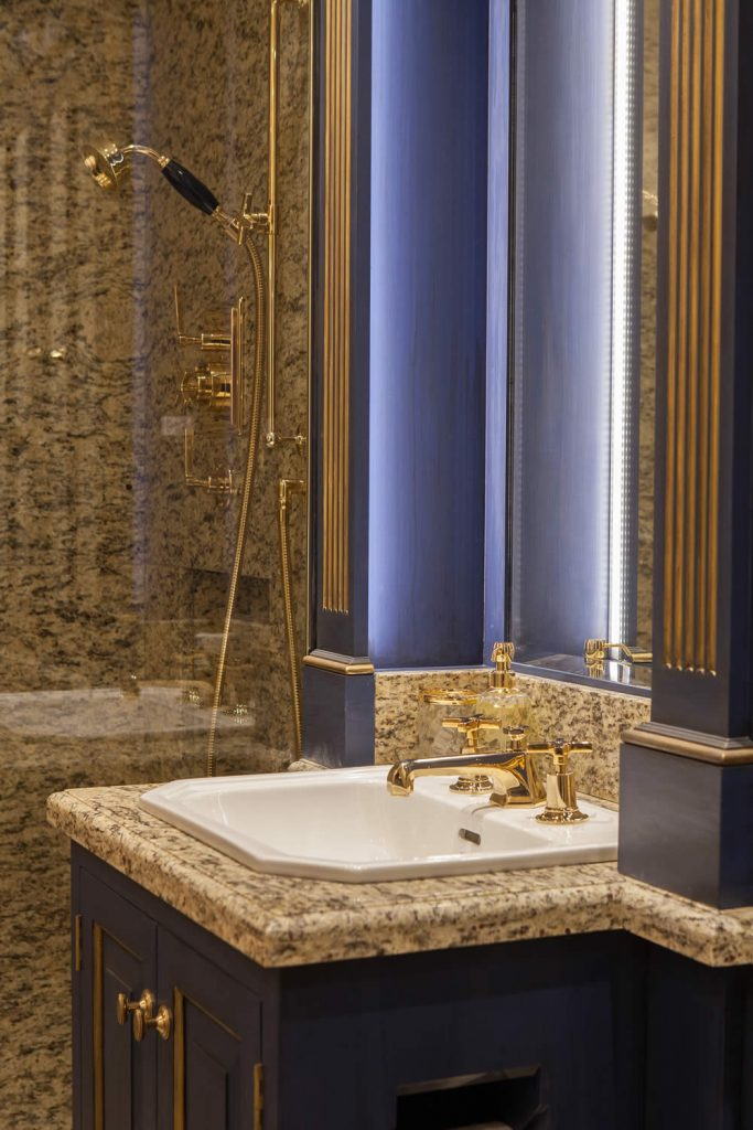 "Interior view of a Bathroom installed with fitted cabinetry and internal doors incorporating raised and fielded door panels set with an Ovalo moulding and projecting fluted pilasters on plain pillar bases. Installation was completed with marble surfaces, gold-plated fixture and fittings, and hand decoration with gilt accents.<br>Private Residence. London. 2015. <br><br> ""I have had the pleasure to work alongside Carmen on many occasions and on many different types of contract, including stately homes and luxurious apartments and houses. In each instance Carmen has proven her professionalism and dedication to the transformation and creation of unique design interiors."" <br> Mr. R. Baker"