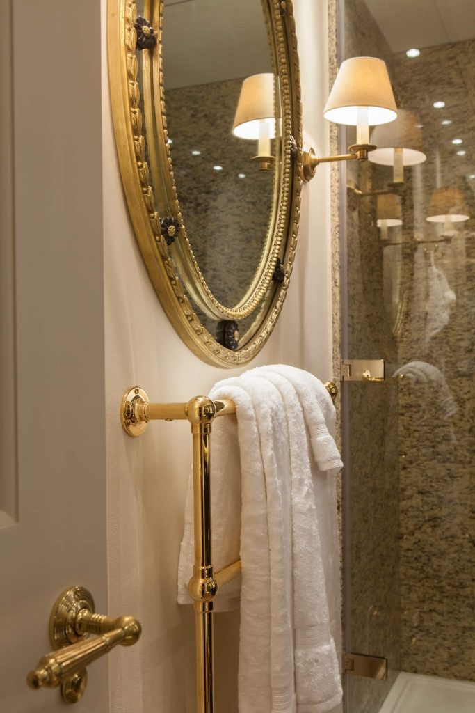 "Interior view of a Bathroom installed with fitted cabinetry and internal doors incorporating raised and fielded door panels set with an Ovalo moulding and projecting fluted pilasters on plain pillar bases. Installation was completed with marble surfaces, gold-plated fixture and fittings, and hand decoration with gilt accents.<br>Private Residence. London. 2015. <br><br> ""Carmen's eye to detail, her feel for the property and application of her customers' requirements is second to none."" <br> Mr. R. Baker"