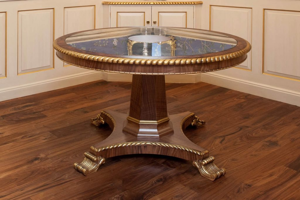 """Design for Georgian style circular pedestal Dining Table featuring a quadraform base, hand carved feet and octagonal tapered pedestal leg. The eglomise mirrored table top is set within a burr walnut border and carved gadrooned front edge accentuated with an ebony detail.The frieze rail incorporates cross banded burr walnut with a carved bead and billet detail.<br>Private Residence. London. 2015. <br><br> """"Carmen's eye to detail, her feel for the property and application of her customers' requirements is second to none."""" <br> Mr. R. Baker"""