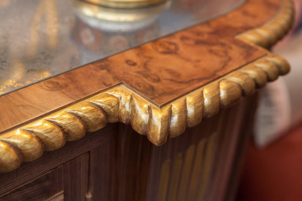 "Detail of drinks cabinet designed to match Georgian-style dining table. Showing an Eglomise mirrored top, burr walnut border, ebony inlay and gadrooned front edge with hand finished fluted pilaster base.<br>Private Residence. London. 2015. <br><br> ""Carmen's eye to detail, her feel for the property and application of her customers' requirements is second to none."" <br> Mr. R. Baker"